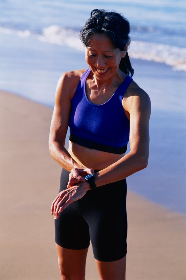Woman standing on beach wearing athletic wear, looking at watch