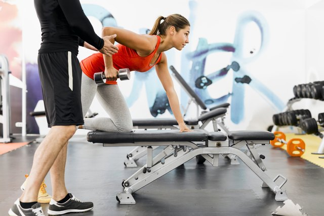 personal trainer working with a client in the gym doing rows