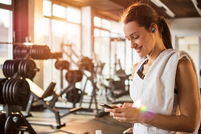 Active girl using smartphone in fitness gym