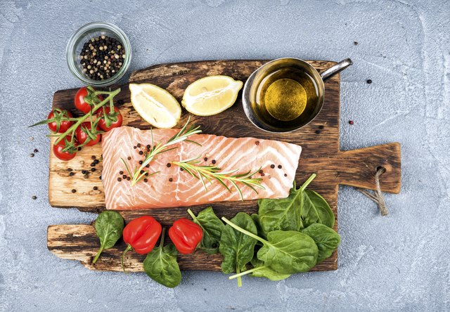 Ingredients for cooking healthy dinner. Raw salmon fillet, spinach, tomatoes, olive oil, lemon, peppers, rosemary and spices on a rustic wooden board