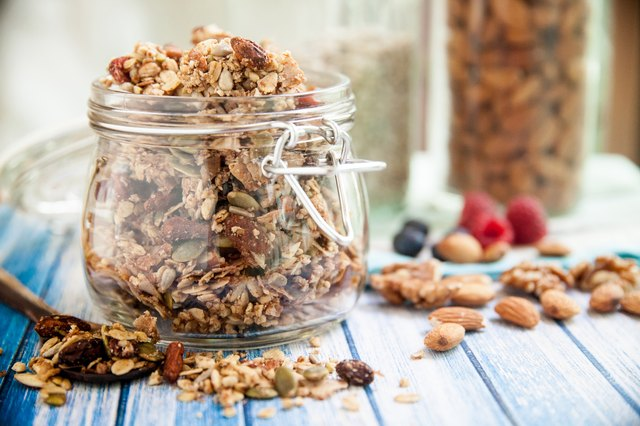 A glass jar in a blue wooden table overfilled with granola
