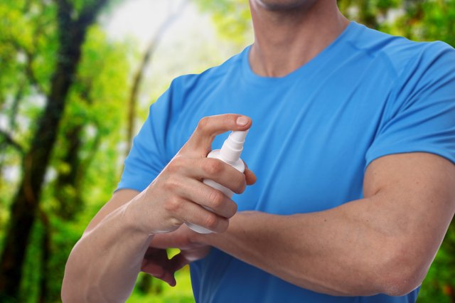 Mosquito repellent. Male using insect repellent spray from bootle in forest.