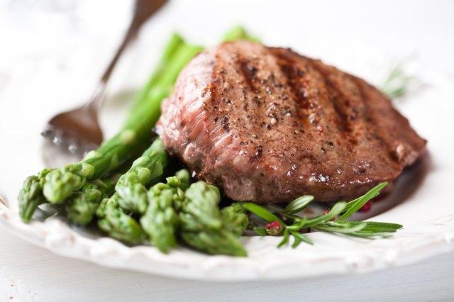 Juicy grilled steak on green asparagus