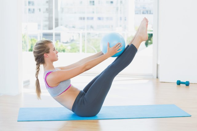 Sporty woman holding ball in fitness studio
