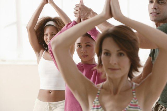 Yoga instructor helping student in row of women