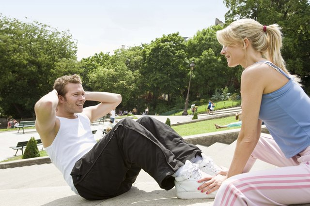 Couple doing sit-ups outdoors