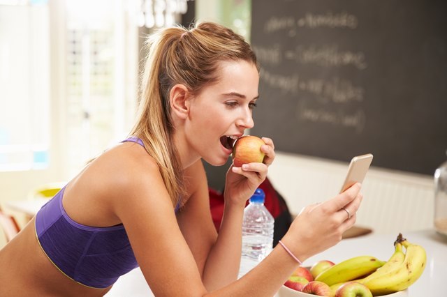 Woman in sports bra eating apple looking at her smart phone