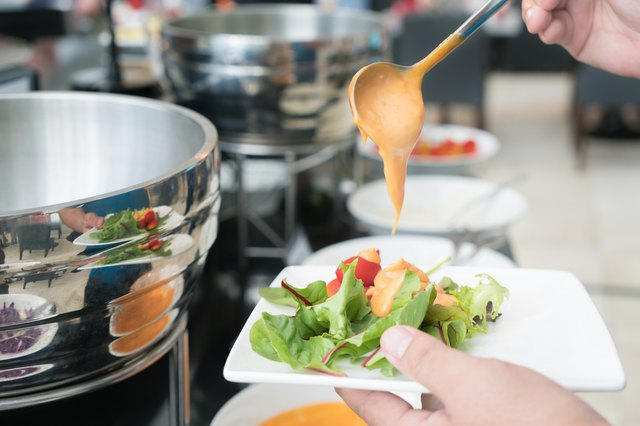 Tablespoon measure of creamy thousand island dressing being poured over fresh garden salad in breakfast buffet at hotel.