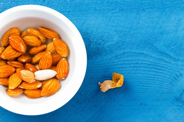 Whole almonds soaked in water over blue table