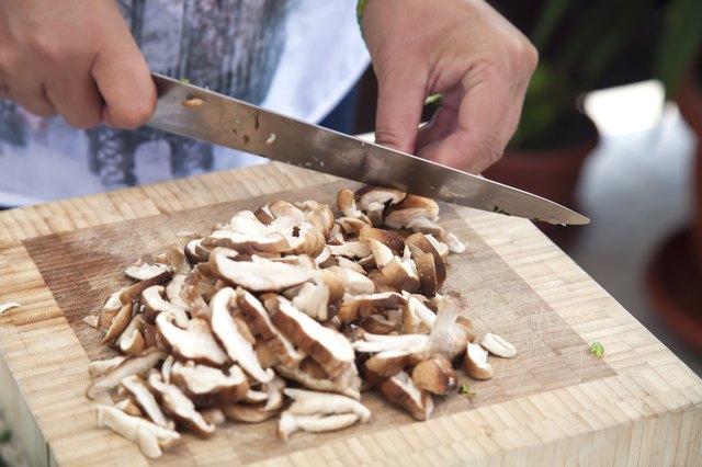 Woman's hands slicing mushrooms.