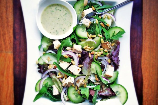 A salad with lettuce, chicken and a variety of vegetables, served with a side of tarragon dressing