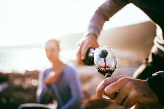 Someone pours a glass of wine at an evening picnic.