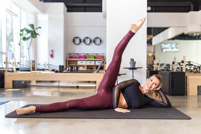 woman doing Develope Kicks on a mat in a Pilates studio